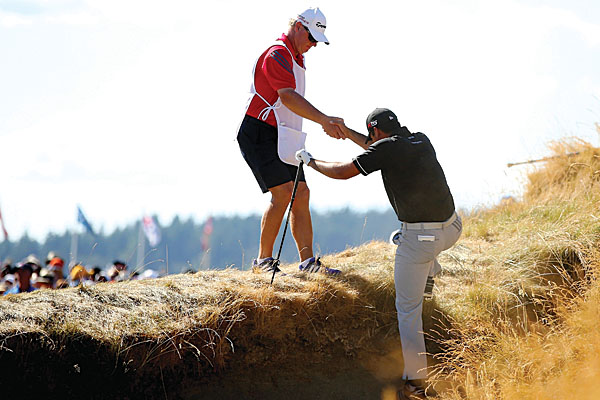 Jason Day requiring the assistance of his caddie to make his escape from a bunker