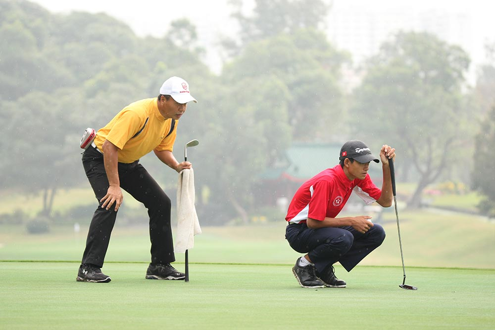 Taichi Kho lines up a putt as Victor reads with care
