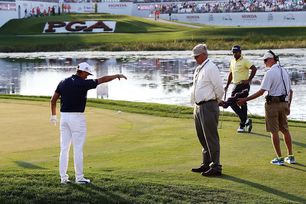 Rickie Fowler gets a ruling from PGA rules official during The Honda Classic