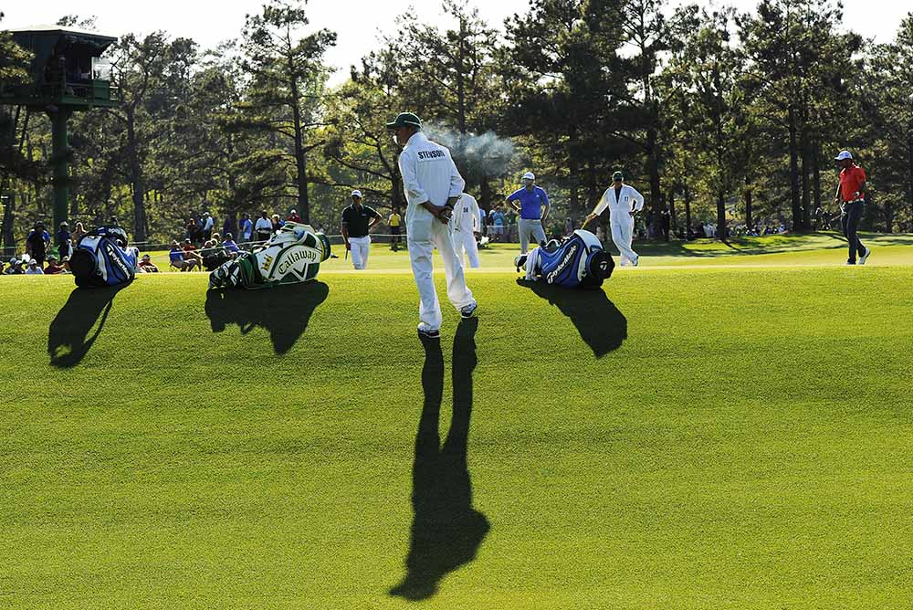 Henrik Stenson's caddie Gareth Bryn Lord (centre) smokes as golfers play during the first round of the 78th Masters Golf Tournament at Augusta