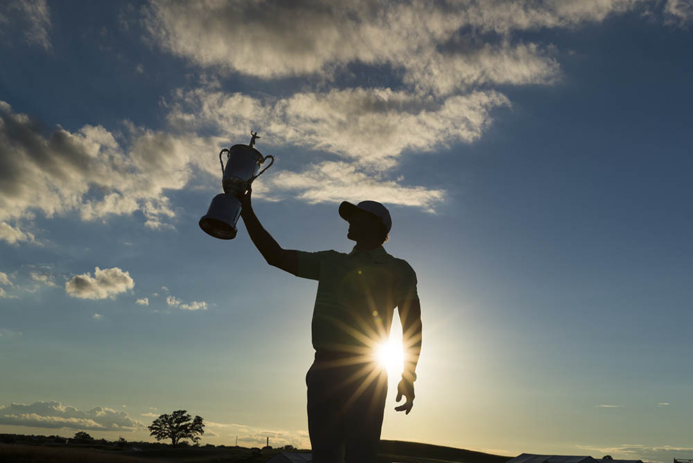 Brooks Koepka holds the trophy at Erin Hills