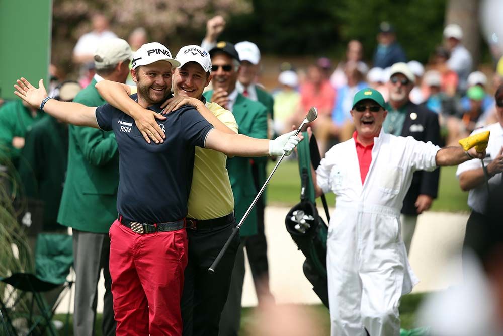 Andy Sullivan celebrates with Emiliano Grillo after hitting a hole in one on the 4th hole during the Par 3 Contest before the start of the 2016 Masters