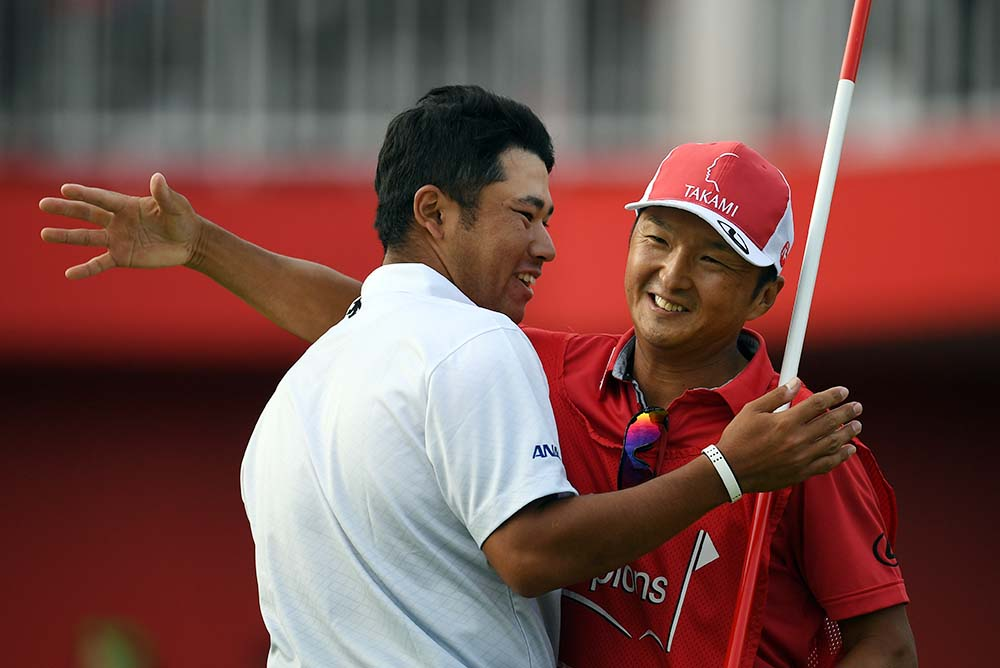 Matsuyama celebrates his victory with his caddy following the final round of 2016 WGC-HSBC Champions