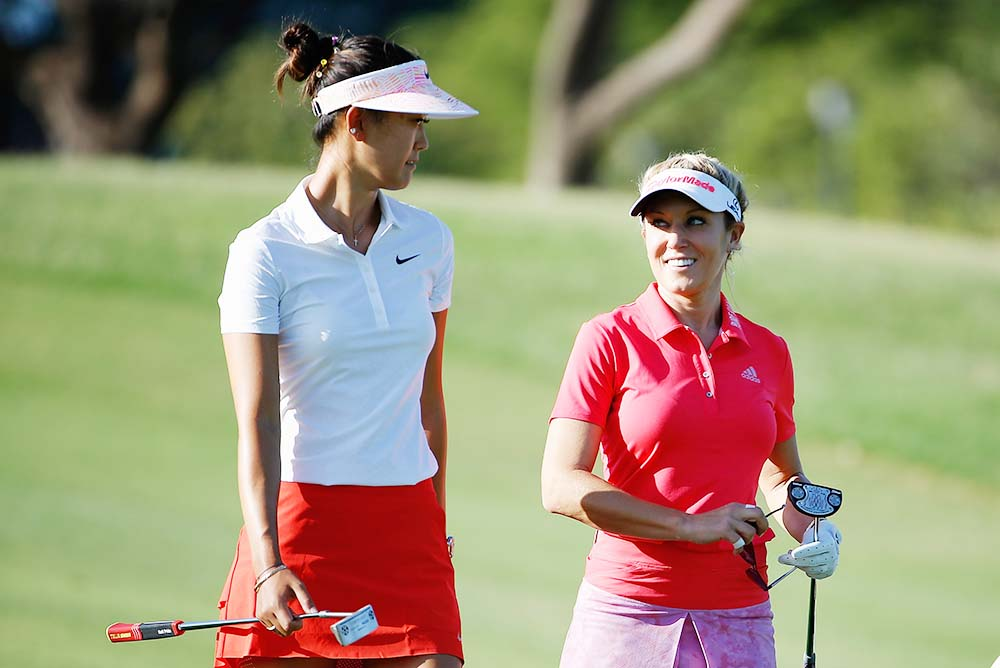 Natalie Gulbis (right) and Michelle Wie (left) talks as they walk down the fairway
