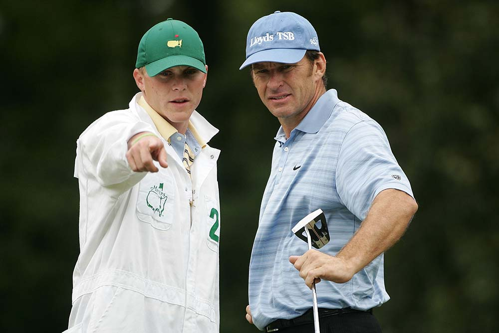 Faldo chats with his caddie Ryan Shaw on the first green during the 2005 Masters