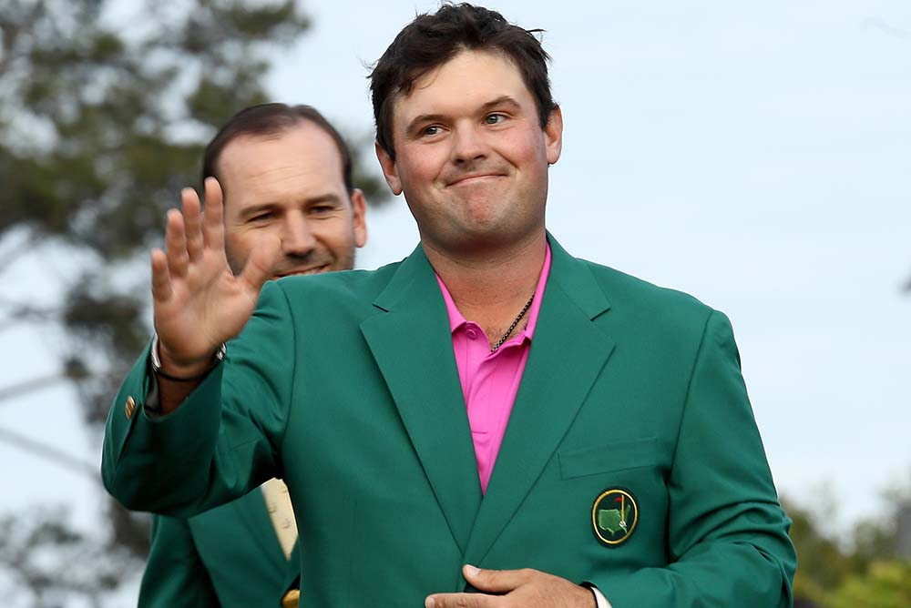Patrick Reed is presented with the green jacket by Sergio Garcia