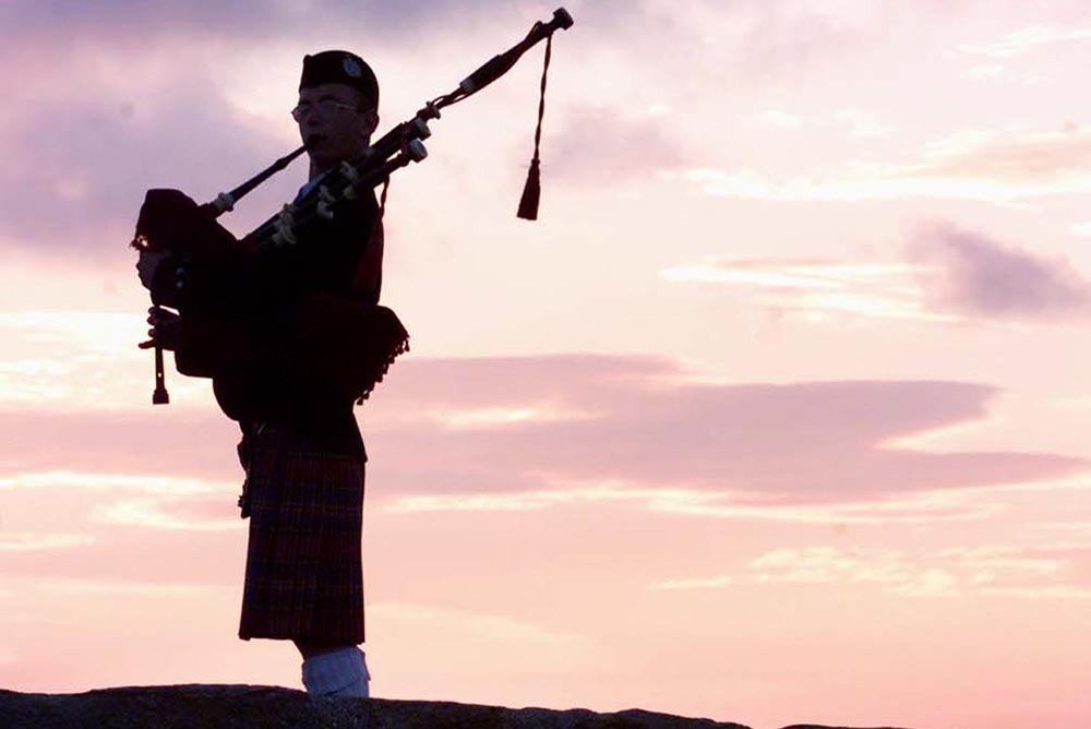 A bagpiper plays on the bridge over Swilken Burn